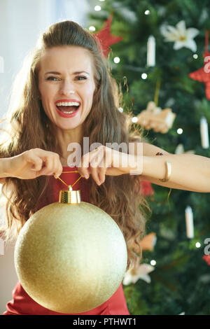 smiling stylish woman in red dress with big gold Christmas ball near Christmas tree - Stock Image