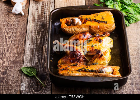 Roasted chicken with seasonal autumn butternut squash, garlic and herbs in baking pan on wooden rustic table, close up, selective focus - Stock Image