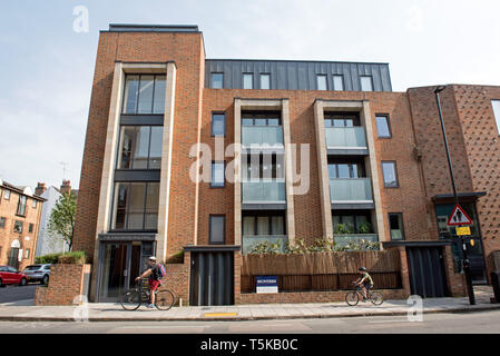 The Kingsbury Building, expensive, modern new build flats or appartments, Drayton Park, Highbury with man and child cycling on pavement in front. - Stock Image