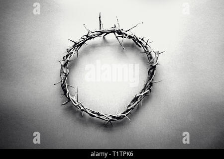 Moody black and white image of crown of thorns like Jesus Christ wore with drops of blood on tips of thorns over grunge background. Perfect for Easter - Stock Image