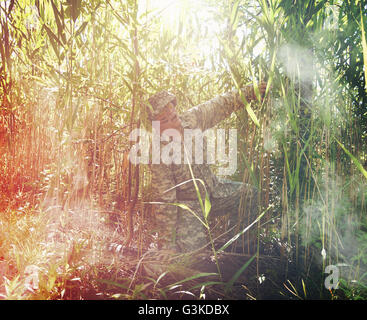 A military army man is in pain and injured in a tall grass field outside for a veteran, trauma or disability concept. - Stock Image