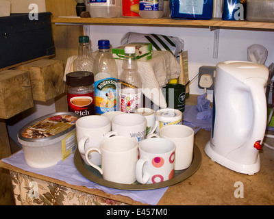 self building house, worker's tea-making corner in workshop, mugs on tray and kettle - Stock Image