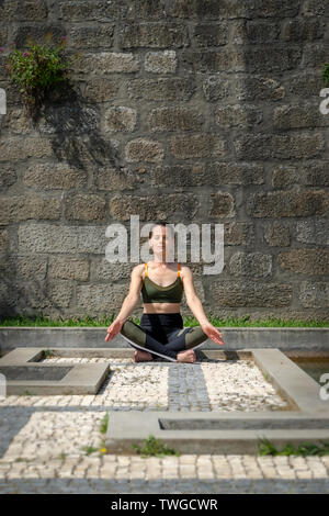 woman meditating practicing yoga outside in an ornate garden setting - Stock Image