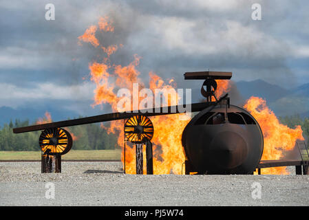 An aircraft fire training simulator is engulfed in flames for U.S. Air Force fire protection specialists, not pictured, assigned to the 673d Civil Engineer Squadron, as they conduct wartime-firefighting readiness training at Joint Base Elmendorf-Richardson, Alaska, Aug. 24, 2018. During the readiness training the Air Force firefighters donned various levels of mission oriented protective posture (MOPP) gear and practiced responding to emergency situations in a simulated toxic environment during a chemical, biological, radiological, or nuclear strike. (U.S. Air Force photo by Alejandro Peña) - Stock Image