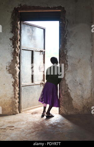 Young Ugandan girl stands in the doorway of her school classrom looking out at other pupils, wearing a bright coloured skirt - Stock Image