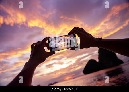 Closeup photo of hands taking a photo from mobile phone. Krabi province, Railay beach on background - Stock Image