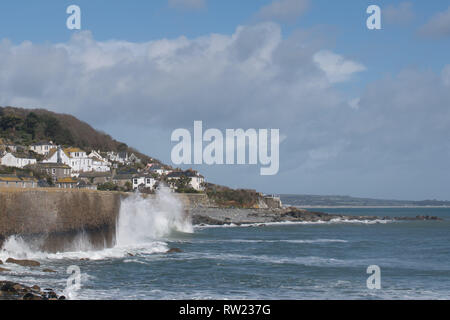 Mousehole, Cornwall, UK. 4th Mar, 2019. UK Weather. A surfer makes the most of the swell left over from storm Freya today. The winds and waves have dropped compared with yesterday. Credit: Simon Maycock/Alamy Live News - Stock Image