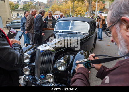 Men standing around and photographing black vintage car near Nydeggbrucke, Bern, Switzerland - Stock Image