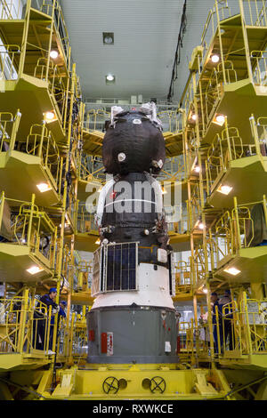 The Russian Soyuz MS-12 spacecraft is prepared for encapsulation into the nose fairing of the booster rocket in the Integration Building at the Baikonur Cosmodrome March 6, 2019 in Baikonur, Kazakhstan. The Expedition 59 crew: Nick Hague and Christina Koch of NASA and Alexey Ovchinin of Roscosmos will launch March 14th for a six-and-a-half month mission on the International Space Station. - Stock Image