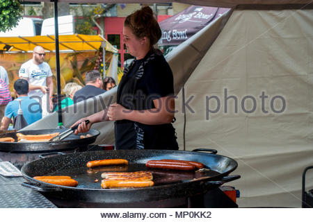 A street food seller tends to a large dish of German sausages at a street food fair in Fleet, Hampshire, UK - Stock Image
