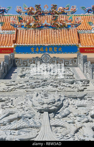 Detail of intricate Chinese Buddhist style dragons carved on stone at the steps of Kuang Im Chapel, in the background. Kanchanaburi, near River Kwai,  - Stock Image