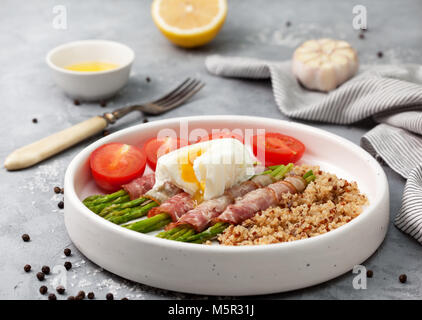 healthy breakfast. Baked asparagus with bacon, quinoa, egg poached in a white bowl on a gray stone background - Stock Image