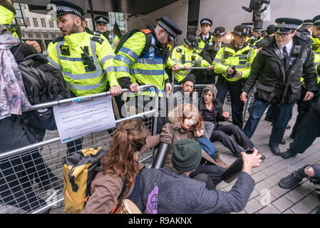 London, UK. 21st December 2018. Climate campaigners from Extinction Rebellion attempt to enter the BBC Plaza calling it to stop ignoring the climate emergency & mass extinctions taking place and promoting destructive high-carbon living through programmes such as Top Gear and those on fashion, travel, makeovers etc. The protest, organised by the Climate Media Coalition (CMC) and its director Donnachadh McCarthy brought mannequins wrapped in white cloth to the BBC representing the bodies of a Greek village killed by fire. Peter Marshall/Alamy Live News - Stock Image