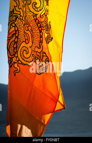 Detail of the Bhutanese Flag, which features the Thunder Dragon, in the morning light in Phobjikha Valley, Bhutan - Stock Image