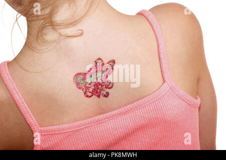 A six year old girl with an easily removed stick on tattoo - Stock Image