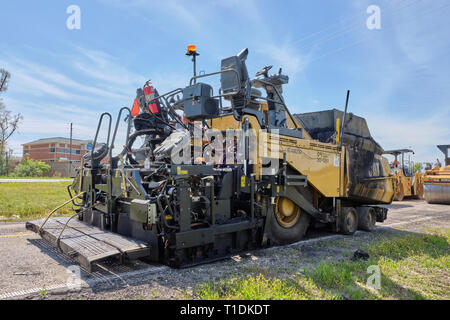Cat AP100F wheeled paving machine or asphalt paving machine parked and idle in Montgomery Alabama, USA. - Stock Image