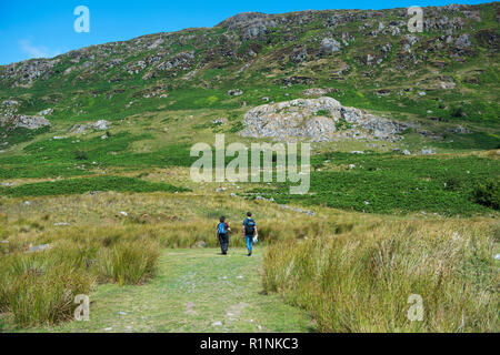 Two hikers walking in the mountains of Snowdonia National Park in North Wales - Stock Image