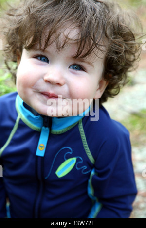 Portrait of blue-eyed baby boy smiling - Stock Image