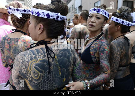 TOKYO, JAPAN - MAY 18: Heavily tattooed Japanese women stand in the street as they wait for the portable shrine in the street of Asakusa during 'Sanja Matsuri' on May 18, 2019 in Tokyo, Japan. A boisterous traditional mikoshi (portable shrine) is carried in the streets of Asakusa to bring goodluck, blessings and prosperity to the area and its inhabitants. (Photo: Richard Atrero de Guzman/ AFLO) - Stock Image