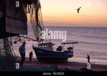 Hastings, East Sussex. 14th Jan, 2019. UK Weather: Fishermen hauling their boat up onto the Stade fishing boat beach to unload the night's catch of fish. Hastings has one of the largest beach-launched fishing fleets in Europe. - Stock Image