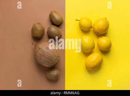 Bunch of raw organic lemons kiwi coconut on duotone yellow brown background. Creative flat lay food poster. Vegan vitamins summer tropical fruits cock - Stock Image