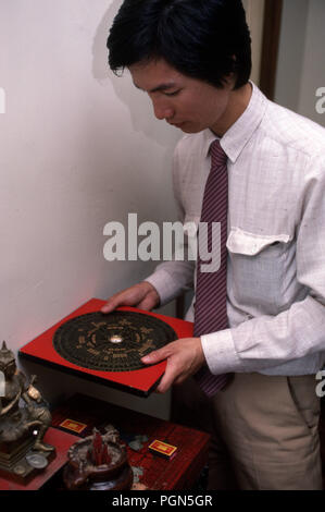 In China a man practises Feng Shui using a Geomancy compass which claims to use energy forces to harmonize individuals with their surrounding environment - Stock Image