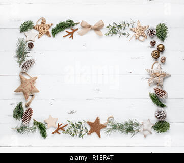 Fir branch and wooden star on wooden background.flat lay - Stock Image
