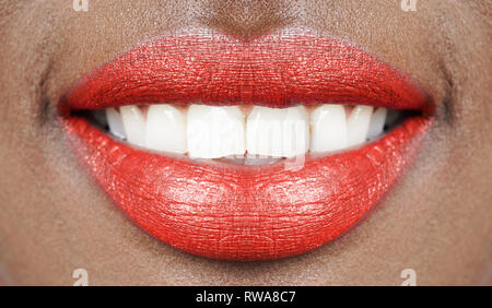 beautiful smile close-up, african woman mouth with full lips, red lipstick and shiny white teeth - Stock Image