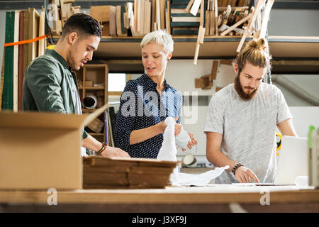 3 young people packing up products in a small warehouse - Stock Image