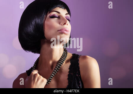 Sensual portrait of a beautiful woman with closed eyes over purple background, gorgeous lady with perfect hairstyle - Stock Image