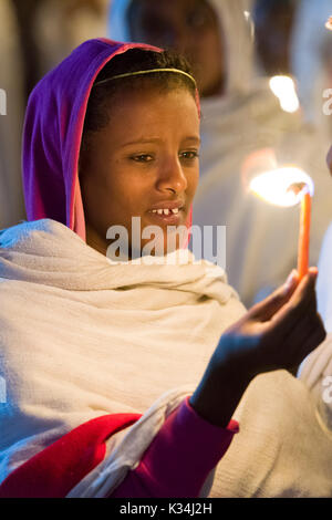 Young female pilgrim holding a candle to signify the resurrection, in the  courtyard of Bet Medhane Alem church, during the prayers on Ethiopia Easter Saturday, Lalibela, Ethiopia - Stock Image