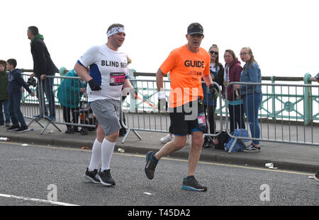 Brighton UK 14th April 2019 -   A visually impaired runner with his guide takes part in this years Brighton Marathon which is celebrating its 10th anniversary Credit: Simon Dack/Alamy Live News - Stock Image