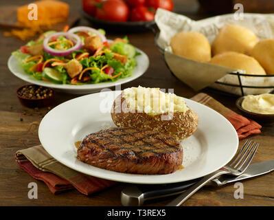 Sirloin steak with baked potato, salad, and dinner rolls - Stock Image