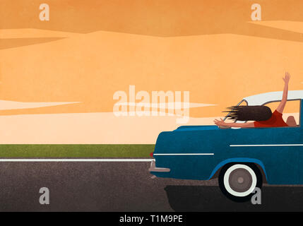 Carefree woman enjoying road trip, leaning out of car window - Stock Image