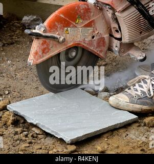 Stone paving slab being cut with a circular petrol powered saw - Stock Image