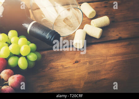red wine bottle with glass and grapes on wooden background - Stock Image