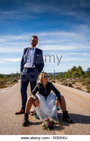 Rocker bride with black leather jacket, boots and sunglasses sitting on a suitcase in the middle of a lonely road and her groom poses behind her. - Stock Image