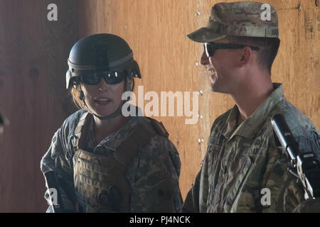 National Training Center, Calif.- Actress Milla Jovovich is briefed by 1st Lt. Elliot Hamilton on room clearing procedures in Razish, National Training Center, on Aug. 31, 2018. Jovovich is here training for a role in an upcoming film. - Stock Image