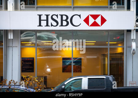 MONTREAL, CANADA - NOVEMBER 5, 2018: Logo of the HSBC Bank, on their main branch in Montreal with cars passing by. HSBC is a british bank spread world - Stock Image