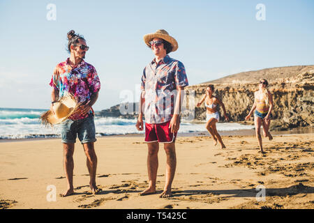 Group of friends have fun together at the beach - men standing and girls behind running to them to play - summer vacation beach concept - millennial p - Stock Image