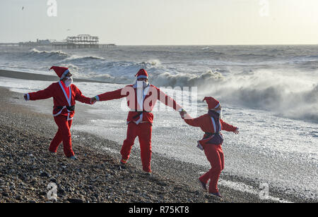 Brighton, Sussex, UK. 08th December 2018. Three Santas go for a walk on the beach in the high winds as they take part in the annual Brighton Santa Dash along the seafront at Hove raising money for the local Rockinghorse charity . Rockinghorse is a Brighton-based charity that has been supporting children in Sussex for over 50 years. Credit: Simon Dack/Alamy Live News - Stock Image