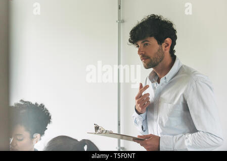 Businessman holding clipboard - Stock Image