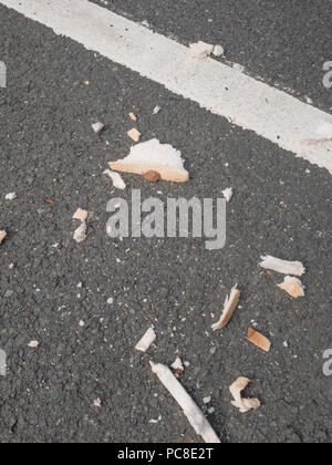 Car parking space in which a piece of bread has been broken into pieces and left to feed birds. - Stock Image
