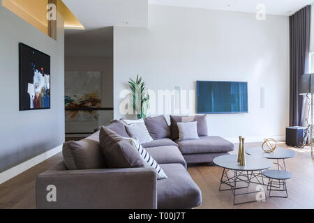Grey velour sectional sofa and three round silver lacquered and metal coffee tables in living room with hickory wood floorboards inside a modern home - Stock Image