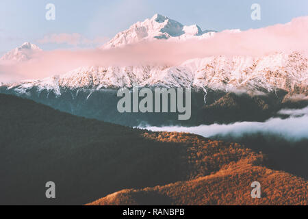 Sunset mountains with clouds landscape Travel aerial view wilderness nature snowy peak and forest tranquil evening scenery - Stock Image