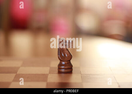 Wooden knight chess piece on a wooden chess board - Stock Image