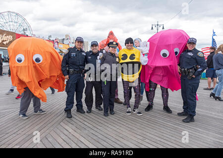 Police and 4 people dressed as Pacman characters pose prior to  the annual Polar Bear Club New Year's day swim in Coney Island, Brooklyn, New York. - Stock Image