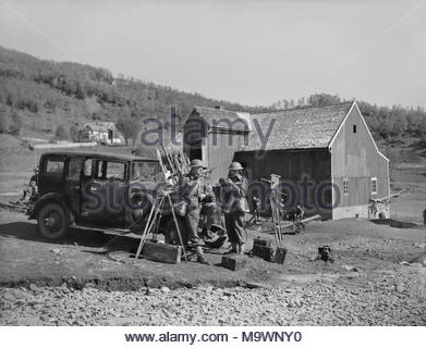 Film and Photography during the Second World War Newsreel filmimg: Cameramen Sydney Bonnett of Gaumont British News (on the left) and Leslie Murray of Universal, with their car and Newman-Sinclair cameras in front of a farm building in Gangsaas Valley, Finmark, Norway. - Stock Image