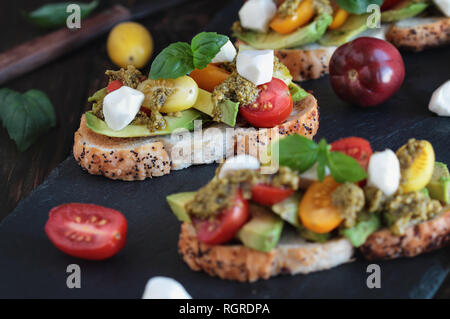 Avocado toast sandwich with avocados, pesto, mozzarella cheese, fresh from the garden basil and heirloom tomatoes, over a rustic wooden background. - Stock Image