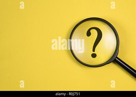 Magnifying glass with QUESTION MARK in focus on yellow background. concept of search and research. - Stock Image